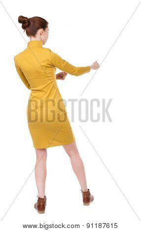 back view standing woman pulling a rope from top or cling to something.  Rear view people collection.  backside view .  Isolated over white background. Girl in mustard strict dress pulls rope on right