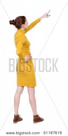 Back view of  pointing woman. beautiful girl.   backside view of person.  Isolated over white background. Girl in mustard strict dress stands sideways resting his hand into the belt and shows up.