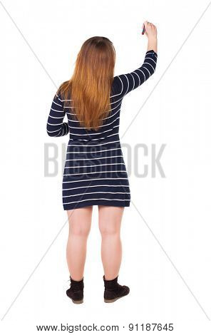 back view of writing beautiful woman. Young girl in dress. Rear view people collection.  backside view of person. Isolated over white background. The girl draws felt-tip pen on the wall to his right.