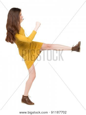 skinny woman funny fights waving his arms and legs. Isolated over white background. Girl engineer in the yellow dress standing right side and hit his left foot.