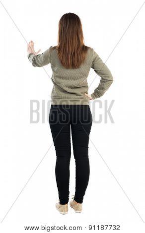 back view of young woman presses down on something. Isolated over white background. Rear view people collection. backside view of person. Confident girl showing stop sign