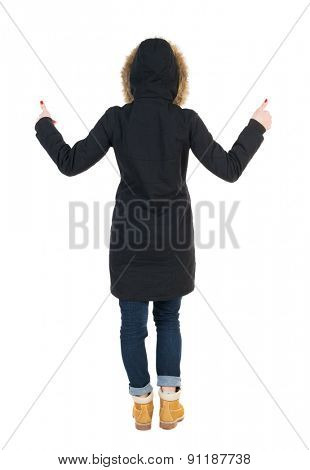 Back view of  woman  in parka thumbs up. Rear view people collection. backside view person. Isolated over white background. Girl in a black winter jacket with a hood with two hands showing thumbs up.
