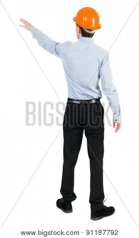 Back view pointing young men in  shirt and helmet. Young guy  gesture. Rear view people collection.  Isolated over white background. Young engineer in shirt and black trousers indicates left hand.