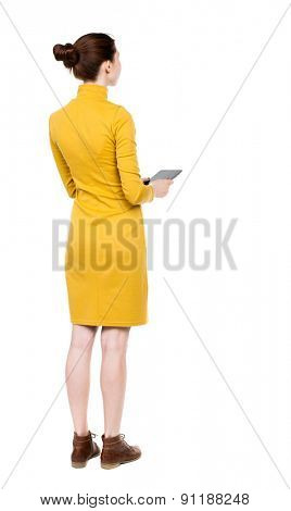 back view of standing young beautiful  girl with tablet computer in the hands of. girl  watching. Rear view people collection.  Girl in mustard strict dress holding plate and looks ahead.