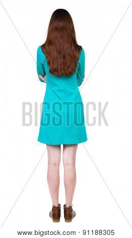 back view of standing young beautiful  woman. Rear view people collection. backside view person.  Isolated over white background. girl in a blue dress with brown boots standing with his arms crossed.