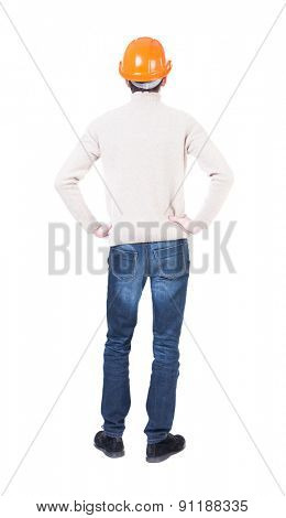 Backview of an engineer in construction helmet stands. Standing young guy. Rear view people collection.  backside view person.  Isolated over white background. Engineer hands on hips looking forward.