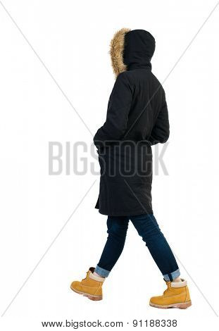 Back view going woman in parka. walking young girl. Rear view people collection.  backside view person. Isolated over white background. Side view of girl in jacket goes with his hands in his pockets