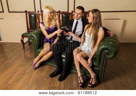 Man and two woman at meeting are drinking wine