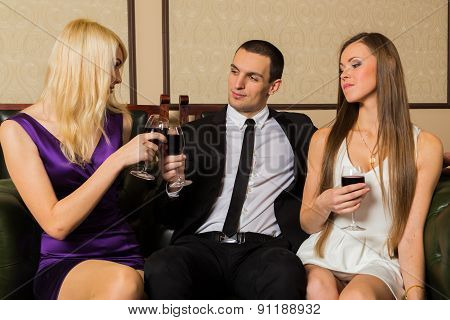 Man and two woman at meeting are drinking wine.