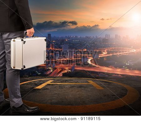 Business Man With Strong Metal Breifcase Standing On Helicopter Pad On Top Of Building Roof With Sun