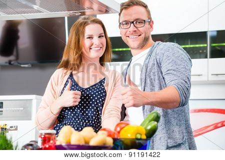 Couple cooking pasta in domestic kitchen