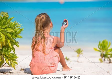 Little girl traveler with a compass in the hand on the beach