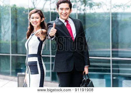 Asian business woman and man outside in front of building