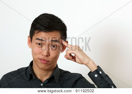 Funny young Asian man pointing his index finger against his temple as crazy sign.