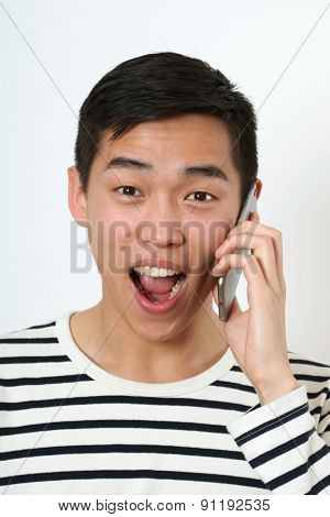 Laughing young Asian man using a smartphone.