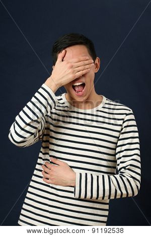 Laughing young Asian man covering his face by palm