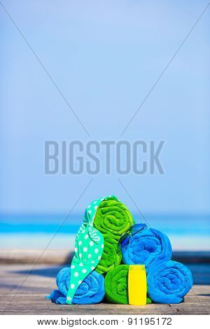 Beach and summer vacation accessories concept - close-up of colorful towels, swimming goggles