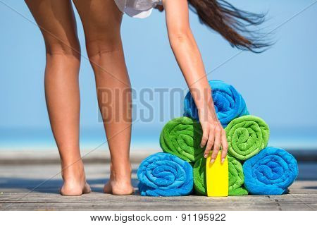 Beach and summer vacation accessories concept - close-up of colorful towels, hat, bag and sunblock