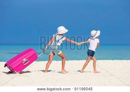 Little tourists girls with big suitcase on tropical white beach