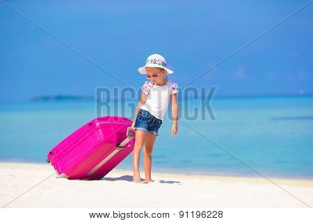 Little adorable girl with big bag on white beach