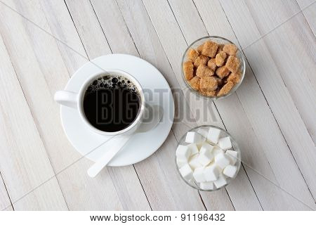 Overhead shot of lumps of raw brown sugar and a white spoon laying of a bed of granulated turbinado sugar. Vertical format with copy space.