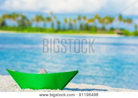 Colorful paper boat on tropical white beach outdoors