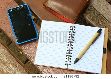 Notebook With Pen, Mobile Phone And Wallet On The Brown Bench