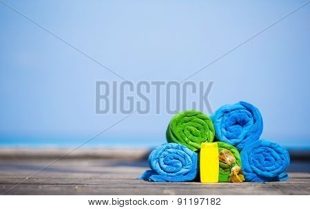 Beach and summer vacation accessories concept - close-up of colorful towels, swimming goggles and su