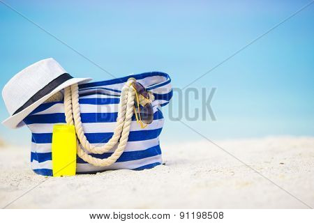 Blue bag, straw hat, sunglasses and sunscreen bottle on white beach
