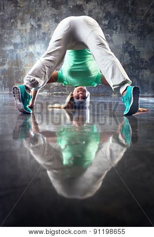 Young smiling woman modern dancer looking on camera upside down. On stone wall background.