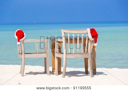 Red santa hats on beach chair at tropical vacation