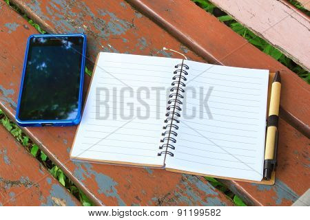 Notebook With Pen And Mobile Phone On The Brown Bench