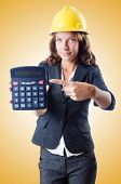 pic of overspending  - Female builder with calculator on white - JPG