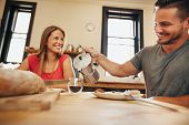 stock photo of breakfast  - Indoor shot of young man pouring coffee into a cup with his girlfriend having breakfast in kitchen at home - JPG