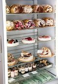 image of cream cake  - Display of traditional Italian semifreddo cakes and desserts in a refrigerator made from semi frozen ice cream and cream whipped into a mousse parfait and flavoured with assorted fruits and flavours - JPG