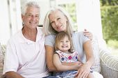 foto of grandparent child  - Grandparents Relaxing On Seat With Granddaughter - JPG