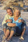 image of couple sitting beach  - Senior Couple On Holiday Sitting On Sandy Beach - JPG
