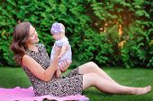 foto of mums  - Mum holds on hands of a little daughter outdoors in park - JPG
