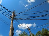 picture of light-pole  - Poles with a lot of wires and electric lamps lighting against a blue sky with wide angle distortion view - JPG