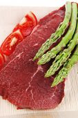 stock photo of white asparagus  - fresh raw beef meat steak fillet on wooden plate with asparagus and tomatoes ready to prepare isolated over white background - JPG