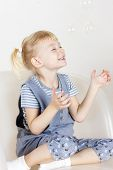 picture of leggins  - little girl sitting on armchair and playing with bubbles - JPG