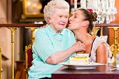 foto of granddaughter  - Senior woman and granddaughter with cake in old fashioned cafe - JPG