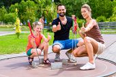 stock photo of miniature golf  - Family playing miniature golf on summer day - JPG