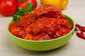 foto of red meat  - Raw marinated meat for bbq with herbs and spices on red tomato sauce - JPG