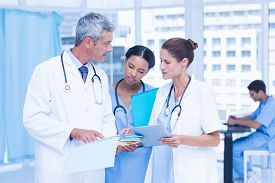 picture of mature adult  - Male and female doctors working on reports in medical office - JPG