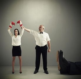 picture of referee  - smiley referee holding winner businesswoman in boxer gloves and looking at her - JPG
