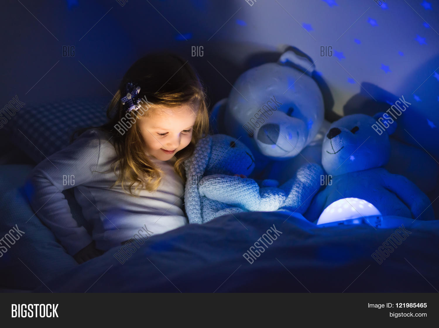 Little girl reading a book in bed. Dark bedroom with night light ...