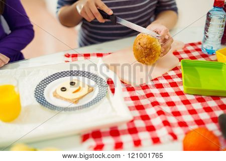 Mother Preparing Healthy And Tasty Lunch Box For Child