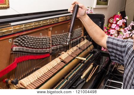 Closeup On Hand Tuning A Upright Piano Using Lever And Tools