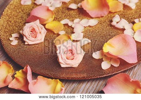 Pink and yellow rose petals in golden bowl on wooden background